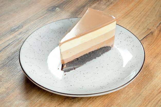 Fatia de bolo mousse de chocolate de três tipos de chocolate em um prato branco sobre um fundo de madeira.