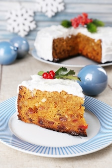 Fatia de bolo no prato com decoração de natal em fundo de madeira