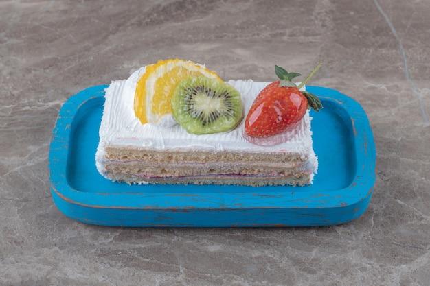 Fatia de bolo pequeno com cobertura de frutas em uma travessa sobre mármore