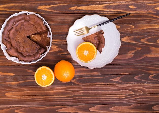Fatia de bolo servido e frutas cítricas cortados ao meio na placa cerâmica branca contra a mesa de madeira