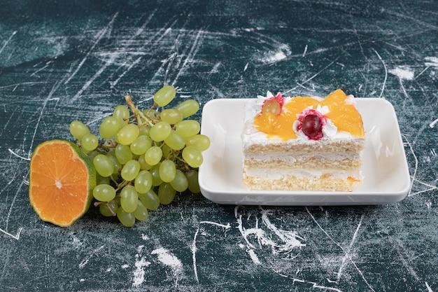 Fatia de bolo, uvas e laranja no espaço azul.