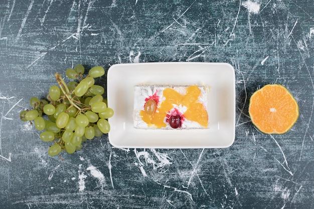 Fatia de bolo, uvas e laranja sobre fundo azul. foto de alta qualidade