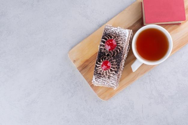 Fatia de bolo, xícara de chá e livro na placa de madeira. foto de alta qualidade
