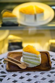 Fatia de bolos de fio de gema de ouro ou fatia de bolo de tanga foi na placa de madeira na loja