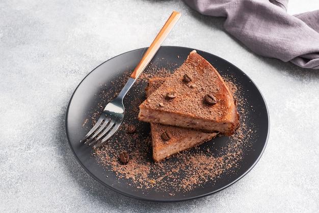 Fatia de caçarola de coalhada de chocolate em um prato, uma porção de bolo com chocolate e café. copie o espaço,