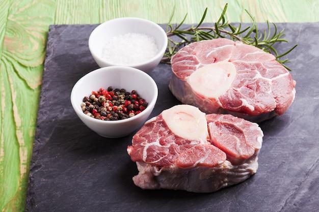 Fatia de carne crua fresca - pernil de vitela cortado em uma placa de ardósia
