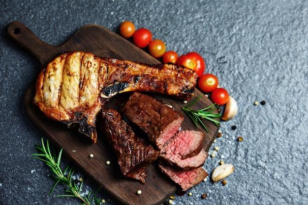 Fatia de carne de bovino grelhada em fundo preto - costeleta de bife e filé de bife assado com ervas e especiarias sirva com vegetais na tábua de madeira