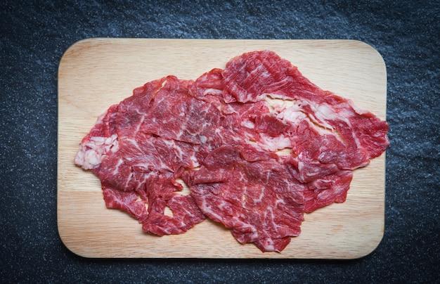 Fatia de carne de bovino na tábua de madeira ou sukiyaki shabu shabu comida japonesa cozinha asiática carne fresca crua