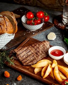 Fatia de carne e batatas assadas