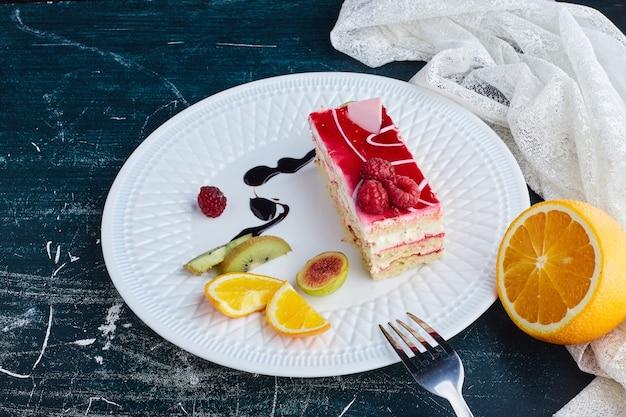 Fatia de cheesecake com calda de framboesa em um prato branco.