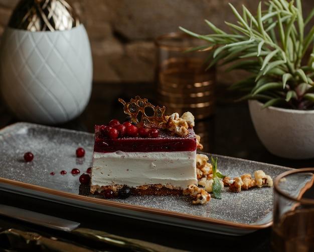 Fatia de cheesecake com molho de frutas vermelhas e louças.