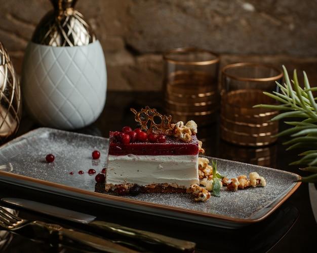 Fatia de cheesecake com molho de frutas vermelhas por cima.