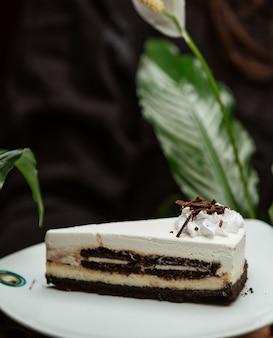 Fatia de cheesecake de baunilha chocolate em um prato branco.