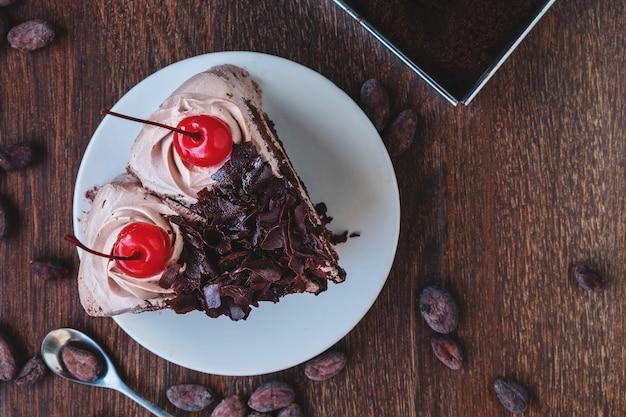 Fatia de cheesecake de chocolate no prato, acima vista sobre um fundo de madeira rústico