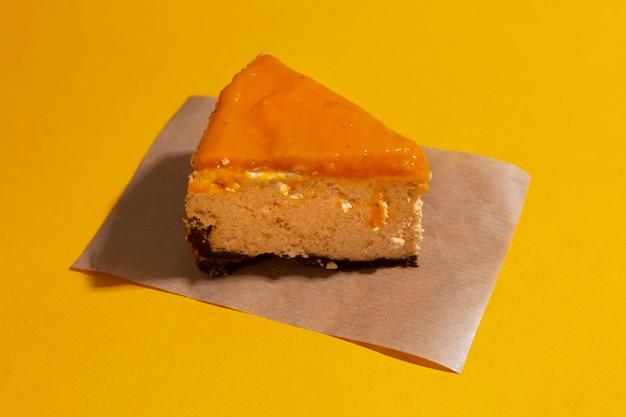 Fatia de cheesecake de manga com cobertura de espinheiro-mar em um fundo laranja sem costura