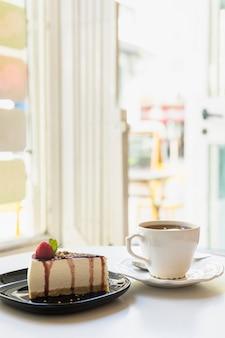 Fatia de cheesecake delicioso e xícara de chá na mesa branca perto de uma porta aberta