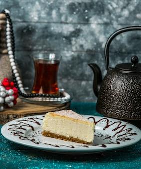 Fatia de cheesecake em chapa branca, servida com chá preto