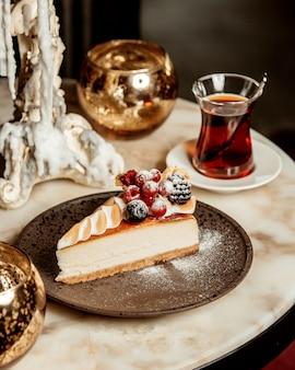 Fatia de cheesecake, guarnecida com frutas, servida com chá preto