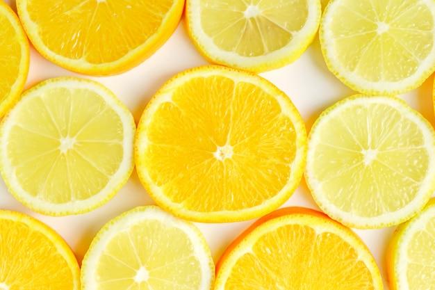 Fatia de citrino, laranjas e limões em fundo branco. cenário de frutas
