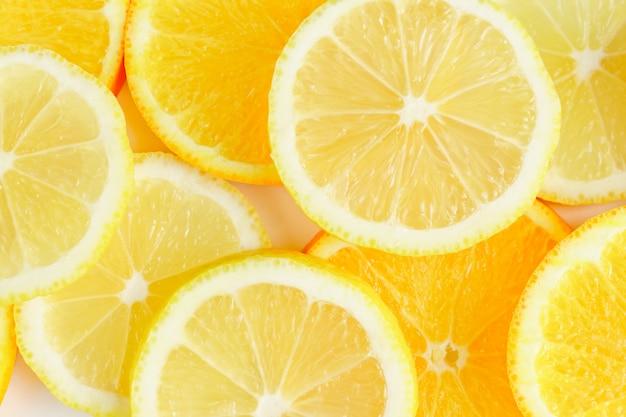 Fatia de citrinos, laranjas e limões em fundo branco,
