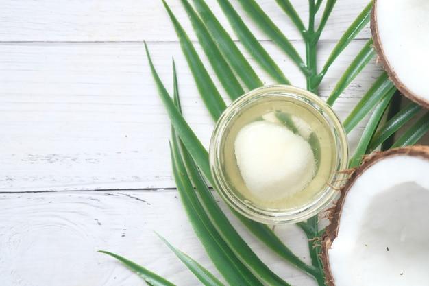 Fatia de coco fresco e garrafa de óleo em uma mesa