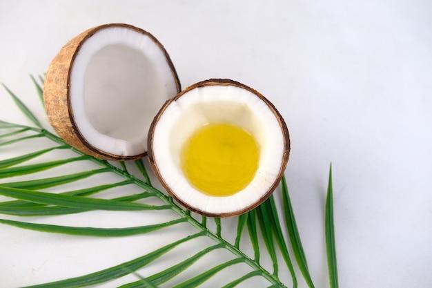 Fatia de coco fresco e óleo em fundo branco com espaço de cópia