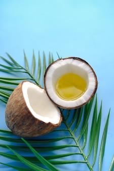 Fatia de coco fresco e óleo sobre fundo azul