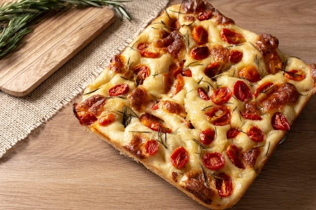 Fatia de focaccia com alecrim, azeite e tomate sobre mesa de madeira