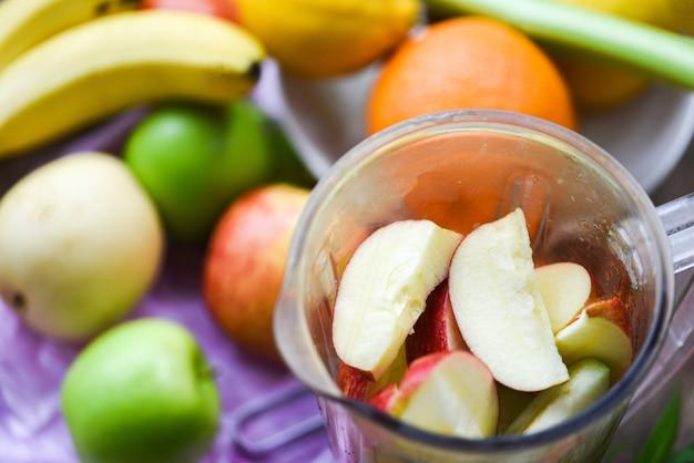 Fatia de frutas frescas no liquidificador preparando ingredientes de verão saudável suco na cozinha