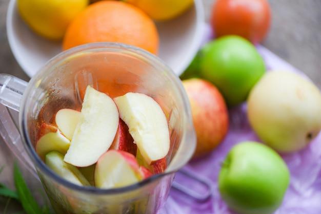 Fatia de frutas frescas no liquidificador preparando ingredientes saudáveis verão suco