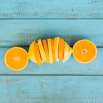 Fatia de frutas laranja e limão no fundo azul de madeira