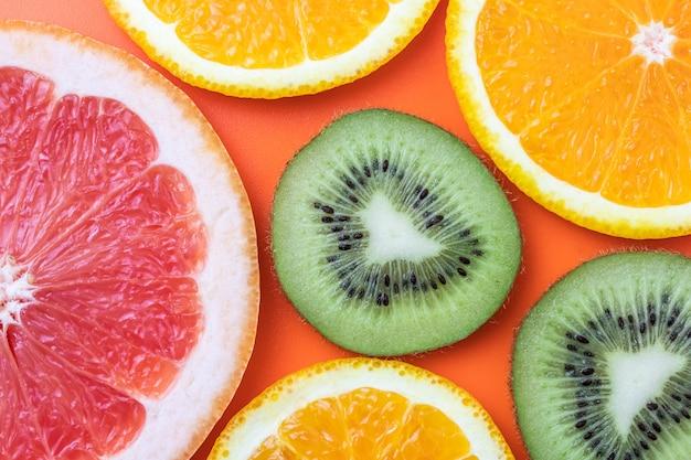 Fatia de kiwi, laranja e toranja na parede brilhante close-up de frutas tropicais exóticas.