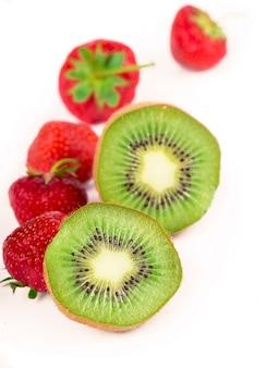 Fatia de kiwi maduro suculento, delicioso e saudável e morango isolado no fundo branco