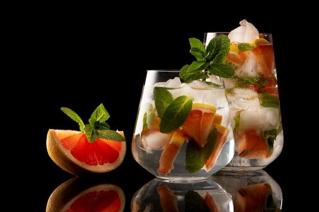 Fatia de laranja e menta e copo com bebida de gelo de laranja e menta isolada no fundo preto