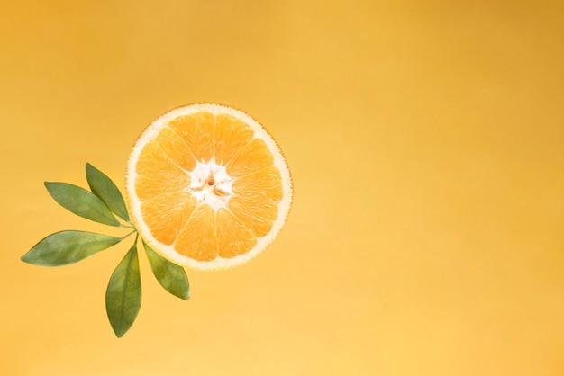 Fatia de laranja fresca com folhas verdes, vista superior.