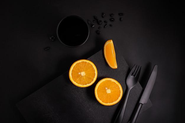 Fatia de laranja na placa preta com vidro preto e talheres preto sobre fundo preto, vista superior