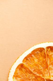 Fatia de laranja seca sobre um fundo marrom claro com espaço para texto. minimalismo, conceito de comida.