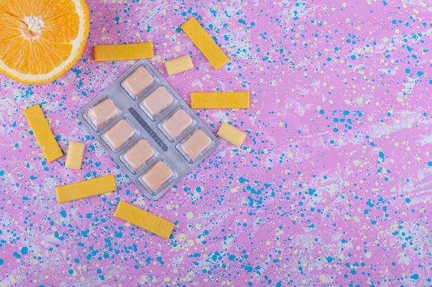 Fatia de laranja, um punhado de chicletes e um pacote de pastilhas de goma em uma superfície colorida