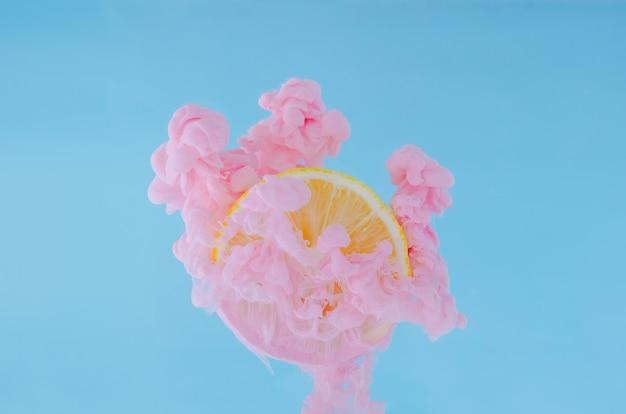 Fatia de limão com foco parcial de dissolver a cor de pôster rosa na água sobre fundo azul.
