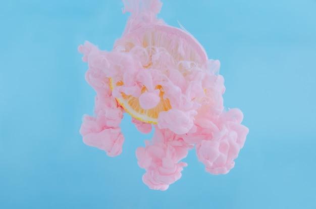 Fatia de limão com foco parcial de dissolver a cor de pôster rosa na água