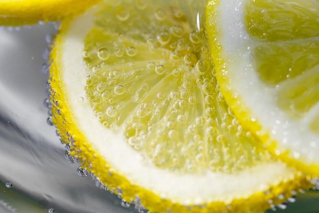 Fatia de limão fresco na água com bolhas