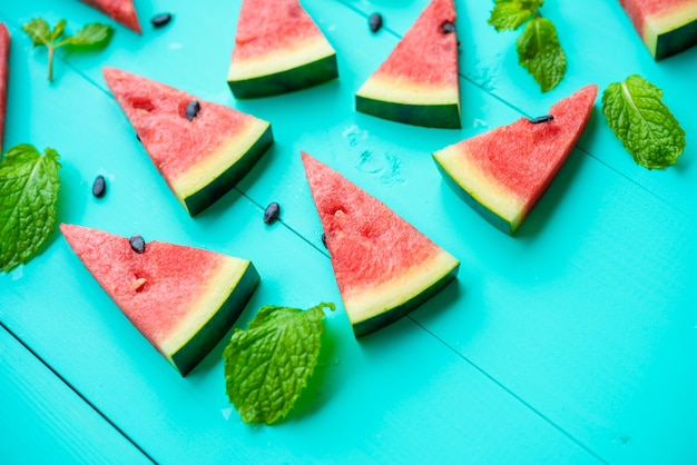 Fatia de melancia com hortelã folhas na mesa azul