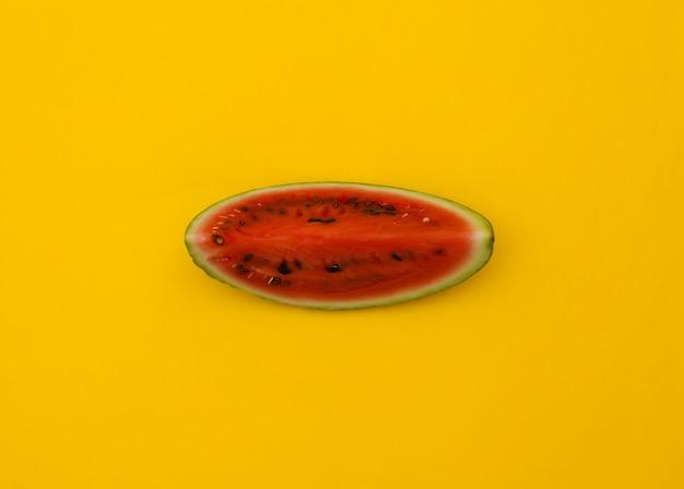 Fatia de melancia contra um fundo amarelo. vista do topo