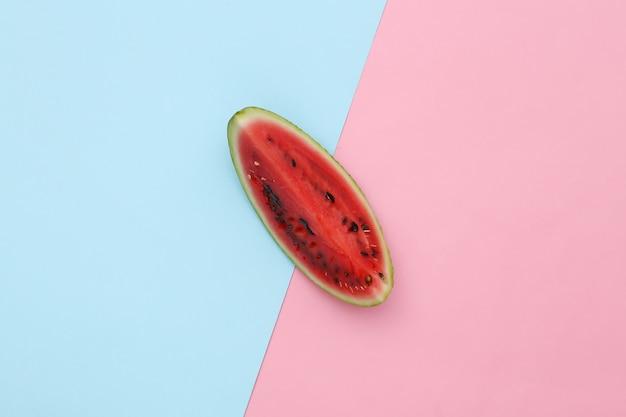 Fatia de melancia contra um fundo azul rosa. vista do topo. minimalismo