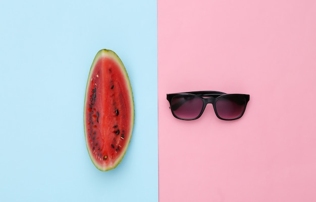 Fatia de melancia e óculos de sol em fundo rosa pastel azul. diversão de verão. vista do topo. postura plana
