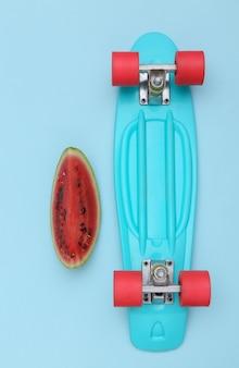 Fatia de melancia e placa cruzadora sobre fundo azul. diversão de verão. vista do topo