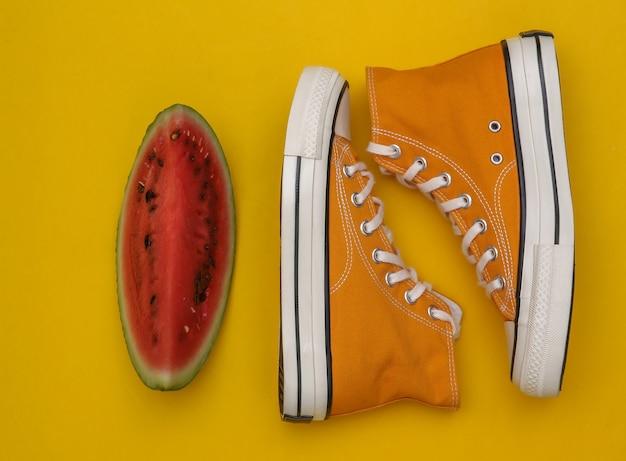 Fatia de melancia e tênis em fundo amarelo. vista do topo. postura plana