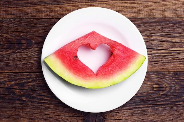 Fatia de melancia em um prato na mesa de madeira