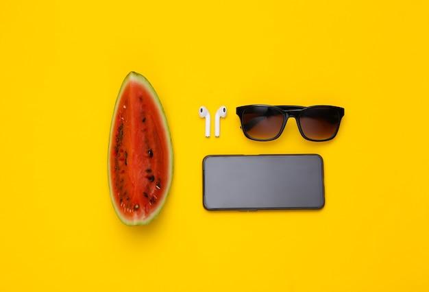 Fatia de melancia, fones de ouvido sem fio, óculos escuros e smartpone em fundo amarelo. diversão de verão. vista do topo. postura plana