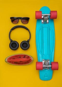 Fatia de melancia madura e acessórios de juventude hipster, placa cruiser em um fundo amarelo. diversão de verão. vista do topo